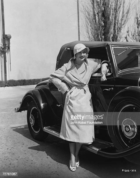 American actress Carole Lombard leans on a car circa 1935