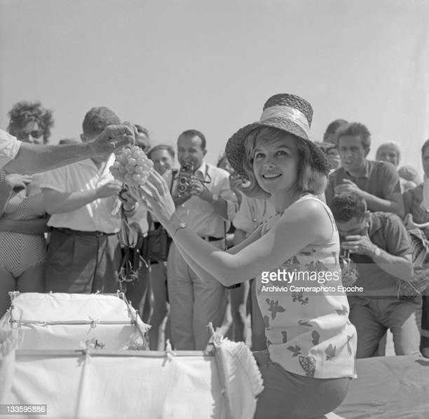 American actress Carroll Baker holding a bunch of grapes during a shooting session on the Lido beach Lido Venice 1961