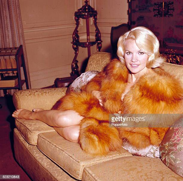 American actress Carroll Baker posed wearing a fur coat whilst sitting on a sofa in London in 1963