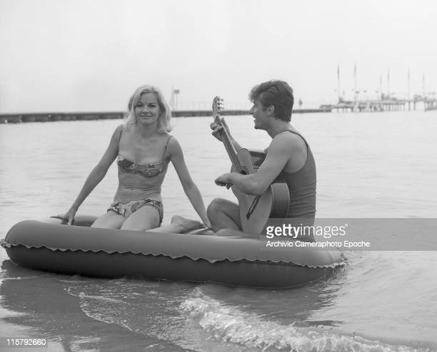 American actress Carroll Baker wearing a fancy bikini and standing on a rubber dinghy with Italian singer Tony Renis playing spanish guitar the Lido...