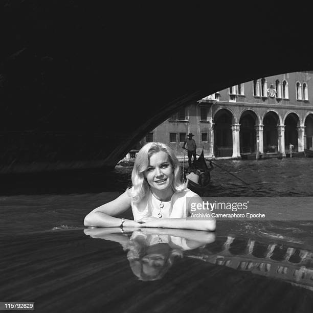 American actress Carroll Baker wearing a white dress portrayed on a water taxi passing under a bridge on the Canal Grande a gondola in the background...