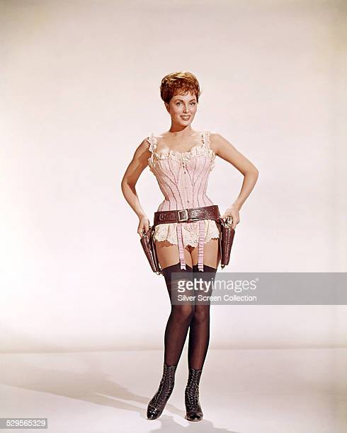 American actress Charlene Holt wearing stockings a corset and a gun belt in a promotional portrait for 'El Dorado' directed by Howard Hawks 1966