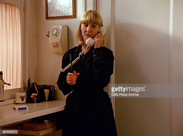 American actress Charlotte Stewart holds a pair of scissors as she speaks on the telephone in a scene from the pilot episode of the television series...