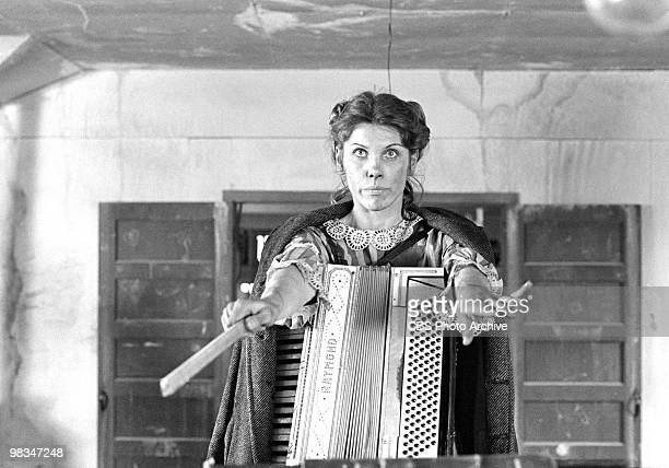 American actress Christine Baranski hold an accordion as she conducts unseen musicians in a scene from the madefortelevsion film 'Playing for Time'...