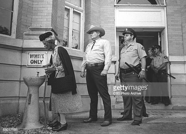 American actress Cicely Tyson takes a drink from a 'whites only' water fountain to the consternation of the local authorities in the...