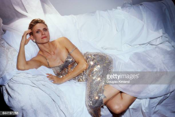 American actress Cindy Pickett wears a silver sequined dress and reclines on a white sofa