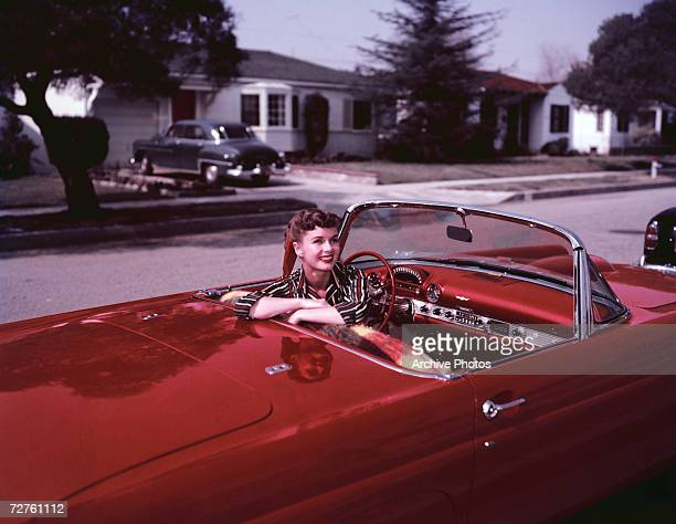 American actress Debbie Reynolds at the wheel of a parked red convertible circa 1955