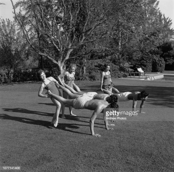 American actress Debbie Reynolds playing wheelbarrow with friends during a pool party 1954 From left to right the women are Reynolds Lori Nelson and...