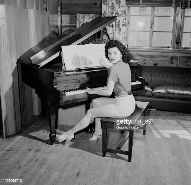 American actress Debra Paget at the piano, circa 1955.