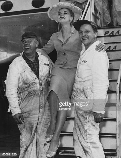 American actress Debra Paget being carried down the steps of an airplane by two engineers after arriving at Berlin Airport July 31st 1958 In Berlin...