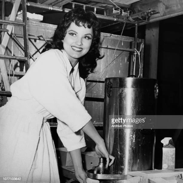American actress Debra Paget helps herself to coffee on the set of the Panoramic Productions film 'The Gambler from Natchez', circa 1954.
