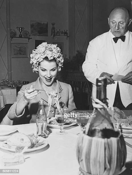 American actress Debra Paget smiling as she eats a plate of spaghetti for the first time during a visit to Rome May 30th 1960