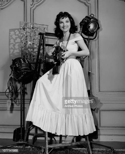American actress Debra Paget takes photographs on the set of the Panoramic Productions film 'The Gambler from Natchez', 1954.
