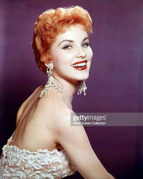 American actress Debra Paget wearing a lacy off-the-shoulder dress and long earrings, circa 1957.