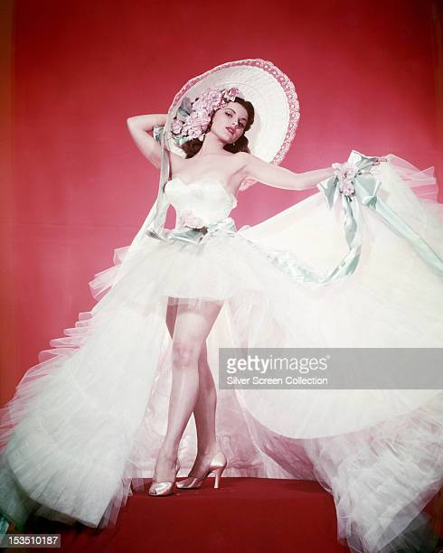 American actress Debra Paget wearing a long, netting skirt, a white bustier and a wide-brimmed sunhat decorated with flowers, circa 1955.
