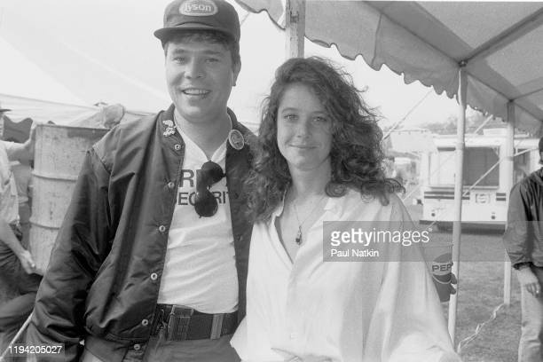 American actress Debra Winger poses with an unidentified man backstage at the inaugural Farm Aid benefit concert at Veteran's Stadium Champaign...
