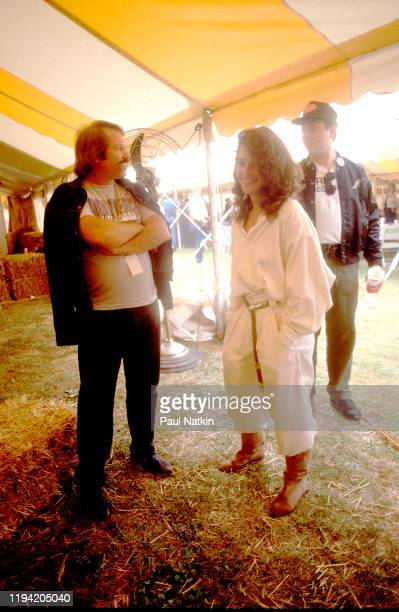 American actress Debra Winger stands with unidentified others backstage during the inaugural Farm Aid benefit concert at Veteran's Stadium Champaign...