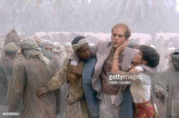 American actress Debra Winger supports American actor John Malkovitch with the help of a local as they're surrounded by a crowd of bedoins during the...