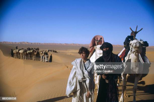 American actress Debra Winger with caravan leader Mohamed Ixa in the desert as a camel caravan pass in the background during the shooting of the...