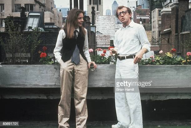American actress Diane Keaton and film director writer and actor Woody Allen each with a drink in their hands talk together on a buildong rooftop in...