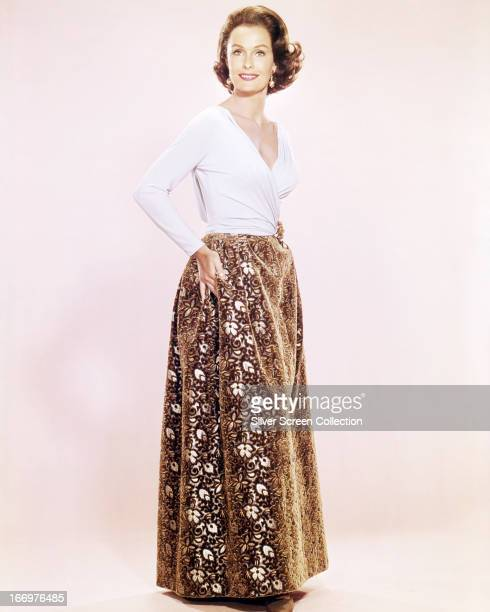 American actress Dina Merrill wearing a white top and ankle-length, floral-patterned skirt, circa 1955.