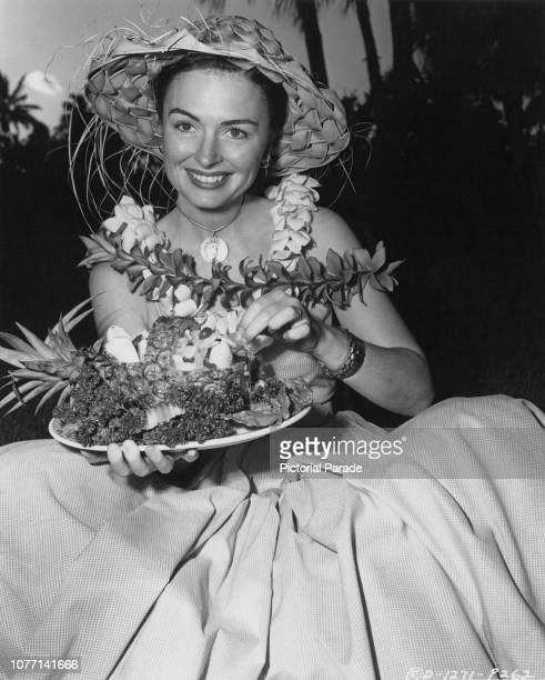 American actress Donna Reed eats a fruit cocktail from a pineapple basket whilst working on the Columbia Pictures production 'From Here to Eternity'...