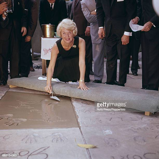 American actress Doris Day pictured holding a trowel as she kneels next to an impression of her hand prints and signature in wet cement during an...