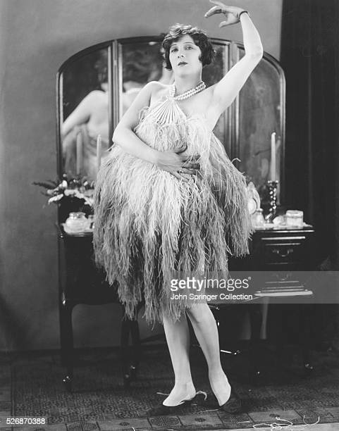 American actress Dorothy Dunbar stands in front of a dressing table posing in an ostrichfeather dress