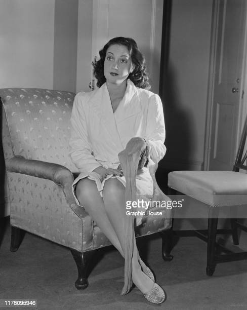 American actress Dorothy Lamour sits in a bathrobe with a single stocking in her hand circa 1945