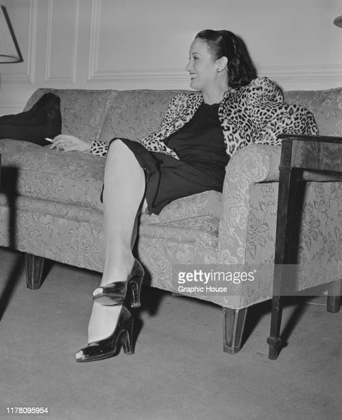 American actress Dorothy Lamour smoking a cigarette in a leopard print jacket circa 1945