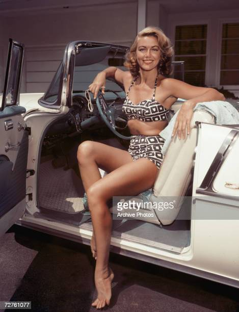 American actress Dorothy Malone at the wheel of a creamcoloured convertible circa 1955