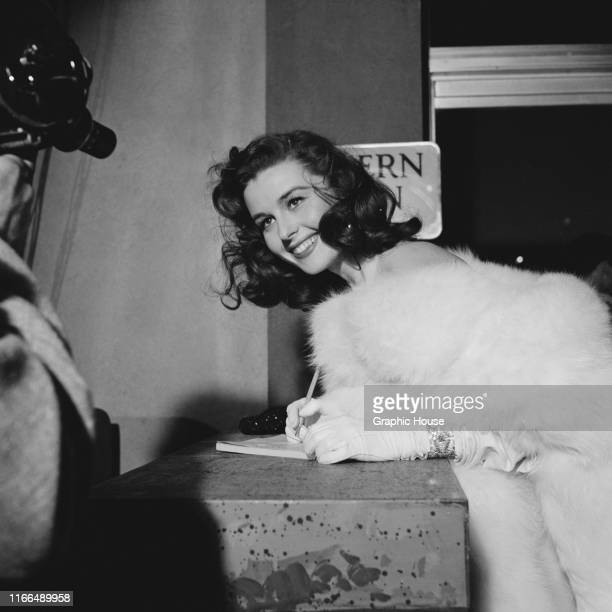 American actress Elaine Stewart signs autographs at the premiere of the film 'Knights of the Round Table' in Los Angeles California 22nd December 1953