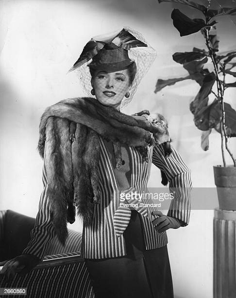 American actress Eleanor Parker wearing a pink and brown jacket with a four skin sable scarf and tall crowned hat of felt with pink and brown wings