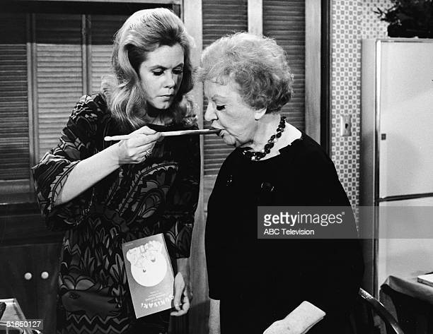 American actress Elizabeth Montgomery feeds American actress Marion Lorne with a wooden cooking spoon as she holds a cookbook entitled 'Sukiyaki the...