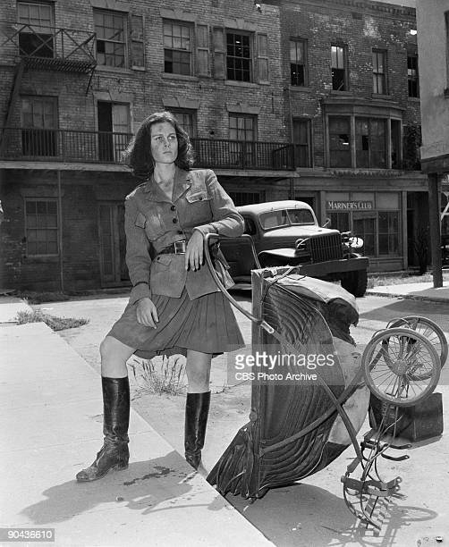 American actress Elizabeth Montgomery leans on an upturned baby carriage in the street in scene from an episode of the television show 'The Twilight...