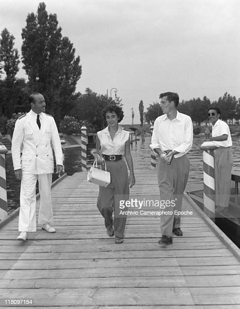 American actress Elizabeth Taylor wearing a sleeveless shirt and wide trousers holding a newspaper and a handbag walking next to her first husband...