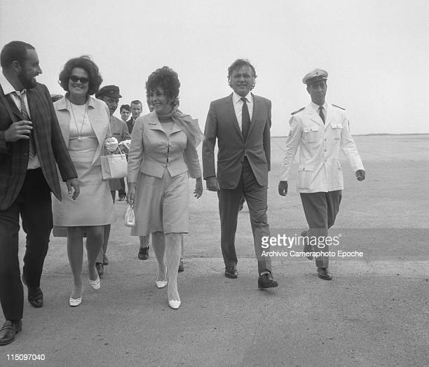 American actress Elizabeth Taylor wearing a tailleur and a foulard holding a handbag walking next to her husband Richard Burton many people around...