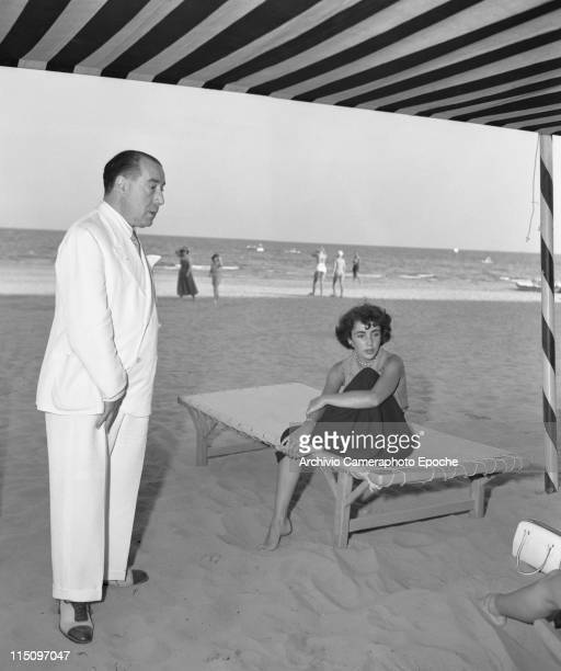 American actress Elizabeth Taylor, wearing wide trousers and sleevesless shirt, sitting on a sunbed on the Lido Beach, with Zucchi Hilton standig...