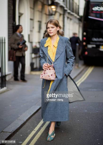 American actress Emma Greenwell wearing yellow dress grey coat seen outside Mulberry during London Fashion Week February 2018 on February 16 2018 in...