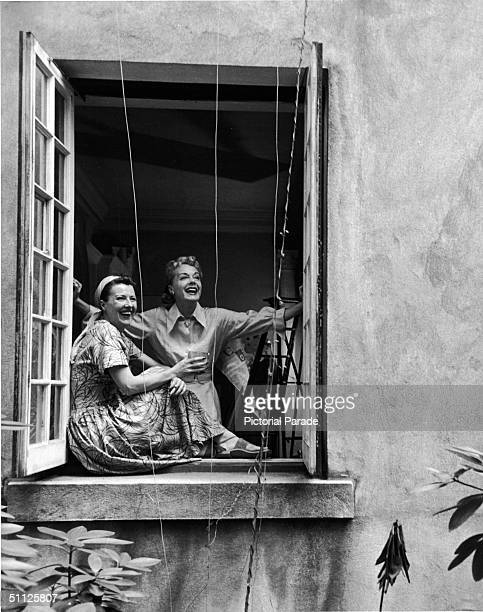 American actress entertainer and author Gypsy Rose Lee and her sister actress June Havoc laugh as they look out of a window late 1960s