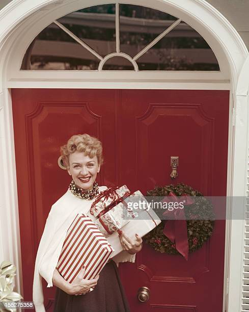 American actress Eve Arden arrives with an armful of presents at Christmas circa 1950