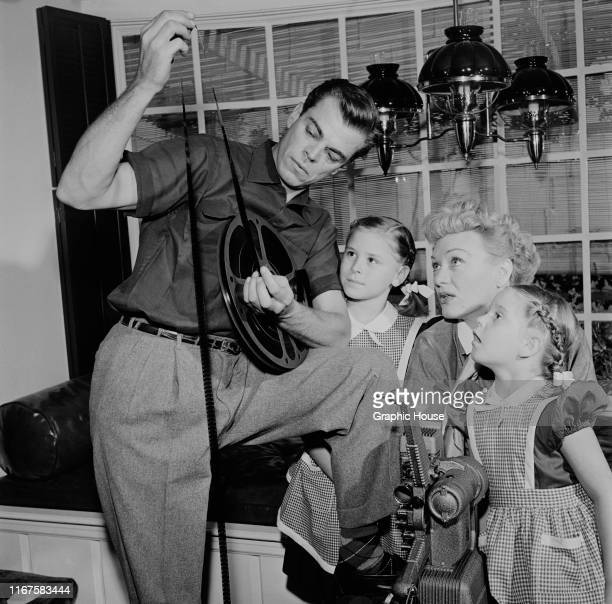 American actress Eve Arden examines some film stock with her husband Brooks West and their two daughters circa 1960