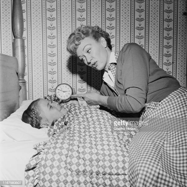 American actress Eve Arden puts one of her daughters to bed circa 1960
