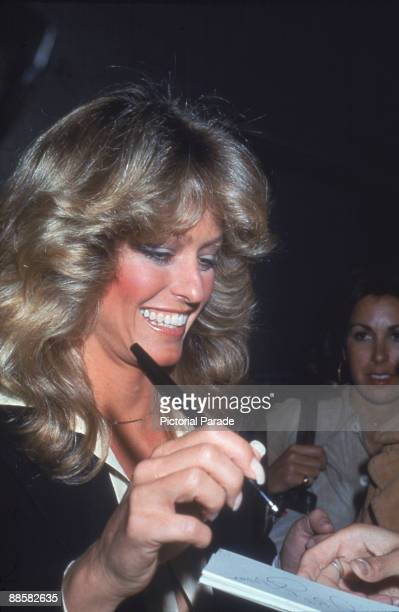 American actress Farrah Fawcett smiles as she signs an autograph on the way out of the studio after taping an episode of the 'Merv Griffin Show'...