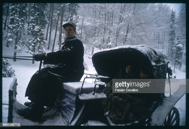 American actress Faye Dunaway and young actor David Eberts ride in a carriage driven by an actor on the set of the 1988 movie Burning Secret or...