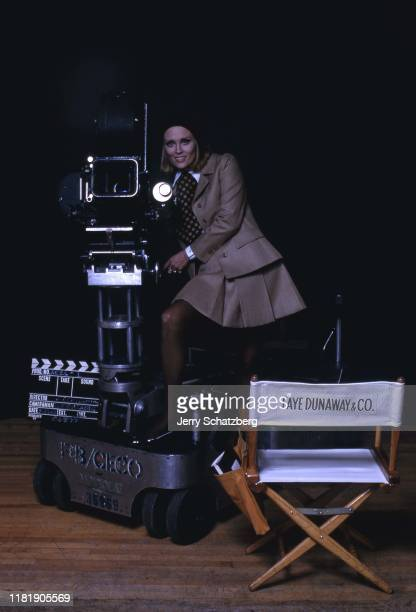 American actress Faye Dunaway in a black beret polka dot tie and brown skirt suit poses on a camera dolly New York New York 1967