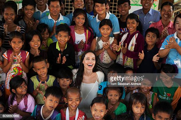 Elevated portrait of American actress film director and United Nations Special Envoy Angelina Jolie as she poses with children and caregivers during...