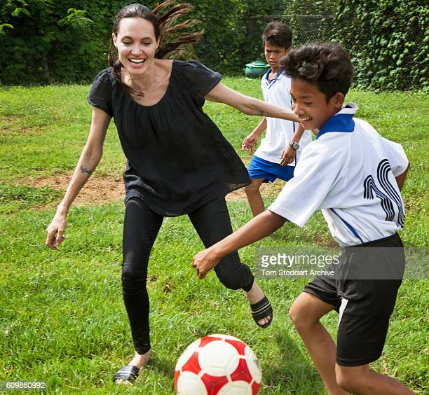 American actress film director and United Nations Special Envoy Angelina Jolie plays soccer with children at a community sports club built by her...