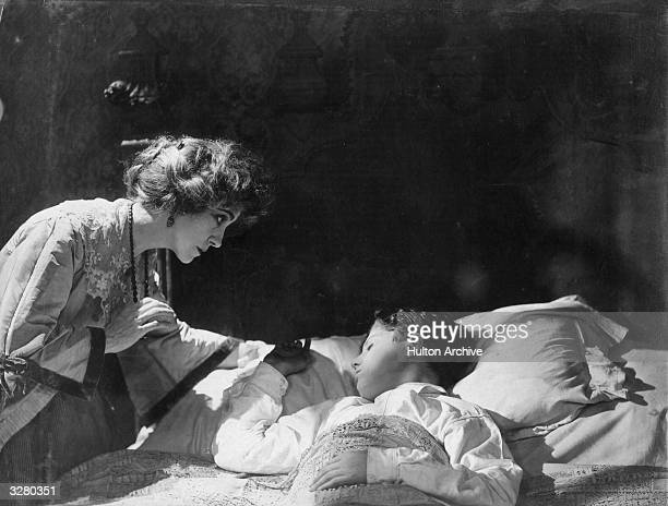 American actress Florence Turner leans over the bed of a sleeping boy in a screen adaptation of Arnold Bennett's book 'The Old Wives' Tale' directed...