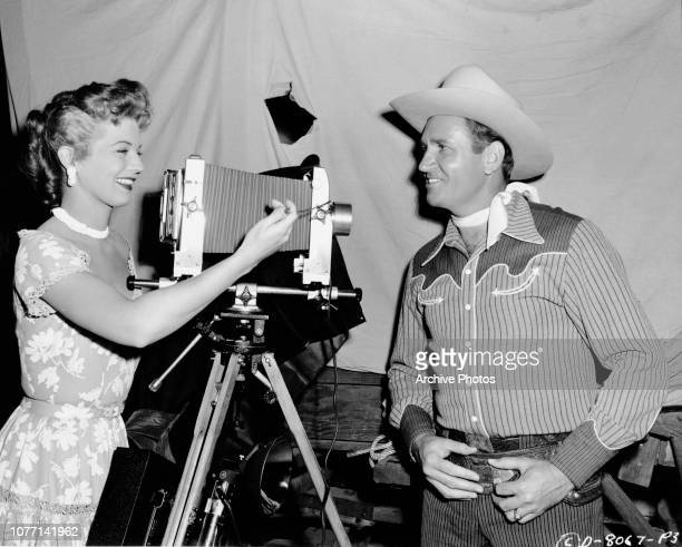American actress Gail Davis takes a photograph of regular costar Gene Autry with an oldfashioned camera circa 1953